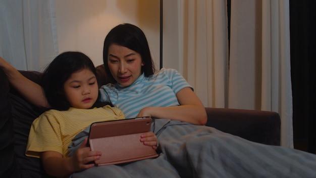 Giovane famiglia e figlia asiatiche felici facendo uso della compressa a casa. la madre coreana si rilassa con il film di sorveglianza della bambina che si trova sul sofà prima di andare a dormire in salone alla casa moderna nella notte. Foto Gratuite
