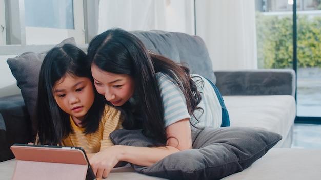 Giovane famiglia e figlia asiatiche felici facendo uso della compressa a casa. la madre giapponese si rilassa con il film di sorveglianza della bambina che si trova sul sofà in salone a casa. divertente mamma e bambino adorabile. Foto Gratuite