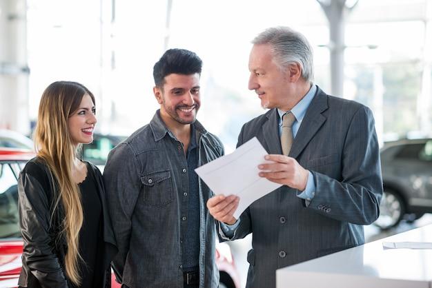 Giovane famiglia felice che parla con il rappresentante in una sala d'esposizione dell'automobile Foto Premium