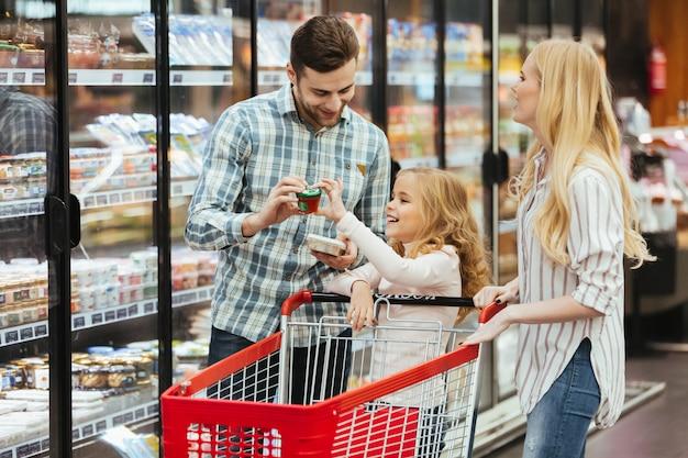 Giovane famiglia felice con un bambino che sta con un carrello Foto Gratuite