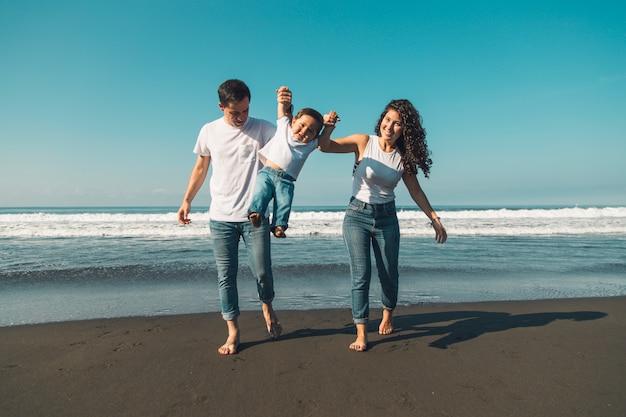 Giovane famiglia felice divertendosi con il bambino sulla spiaggia soleggiata Foto Gratuite