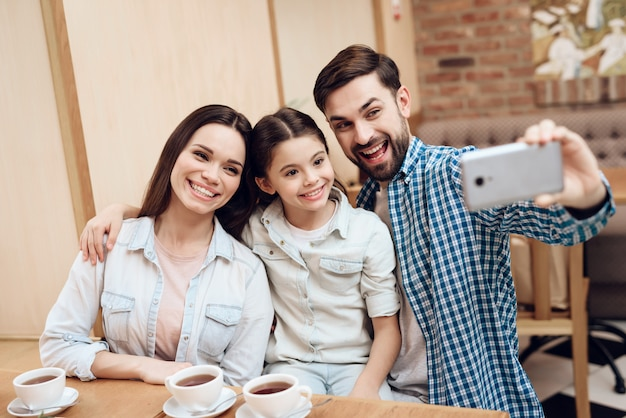 Giovane famiglia felice prendendo selfie in caffetteria. Foto Premium