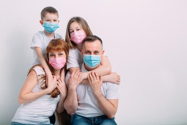 Giovane famiglia in maschere mediche durante la quarantena domestica. Foto Premium