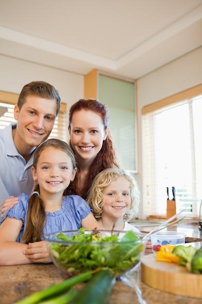 Giovane famiglia in piedi dietro il bancone della cucina Foto Premium