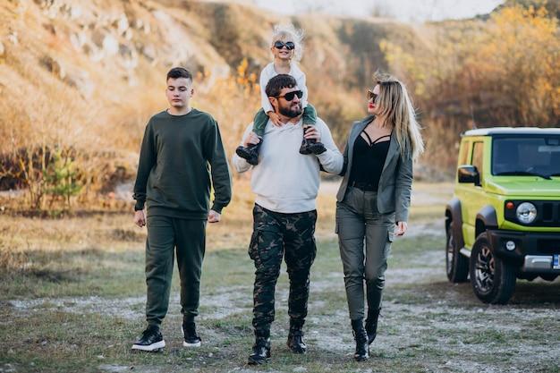 Giovane famiglia moderna che viaggia in auto e si ferma per una passeggiata nel parco Foto Gratuite