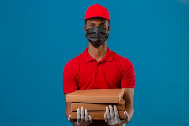 Giovane fattorino afroamericano che indossa la camicia e il cappuccio di polo rossi in maschera protettiva e guanti che stanno con la pila di scatole della pizza con il fronte serio sopra il blu isolato Foto Gratuite