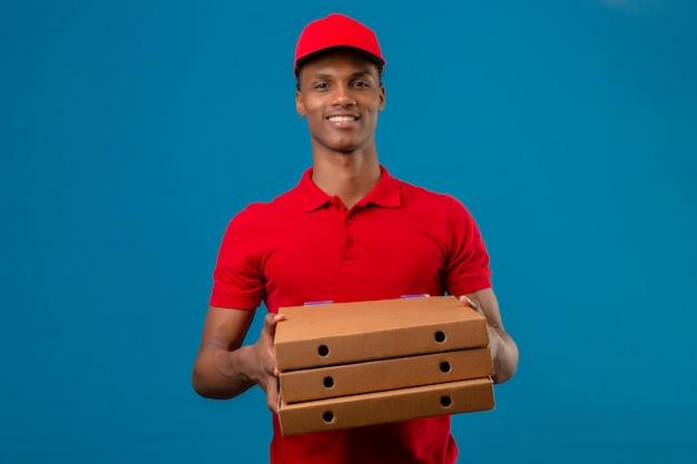 Giovane fattorino afroamericano che indossa la pila della tenuta della camicia e del cappuccio di polo rosso di scatole della pizza con il grande sorriso sopra il blu isolato Foto Gratuite