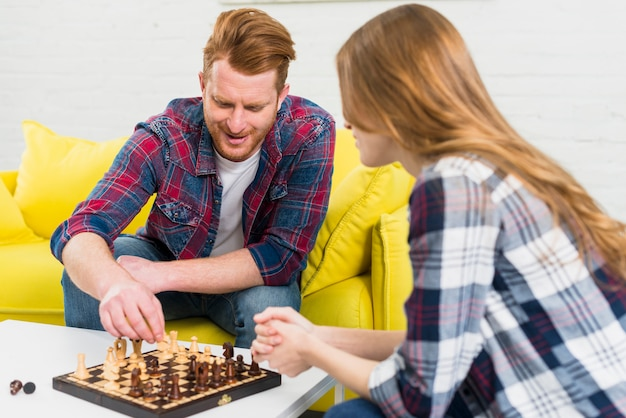 Giovane felice che gioca gli scacchi con la sua ragazza a casa Foto Gratuite