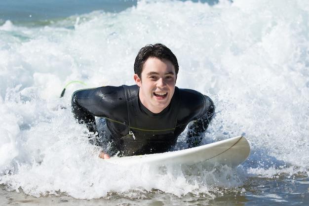 Giovane felice che nuota sulla tavola da surf nell'oceano Foto Gratuite