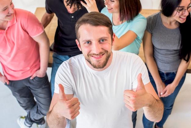 Giovane felice che sta con gli amici che mostrano gesto di pollice che esamina macchina fotografica Foto Gratuite