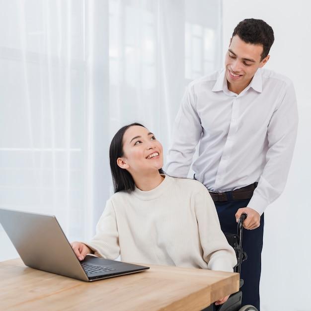 Giovane felice che sta dietro la donna asiatica che utilizza il computer portatile sulla tavola di legno Foto Gratuite