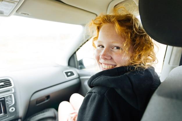 Giovane femmina allegra che si siede in macchina Foto Gratuite