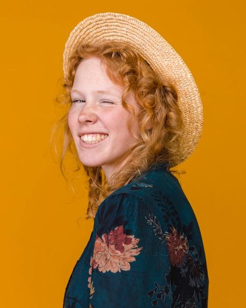Giovane femmina attraente in cappello che sbatte le palpebre sulla macchina fotografica Foto Gratuite