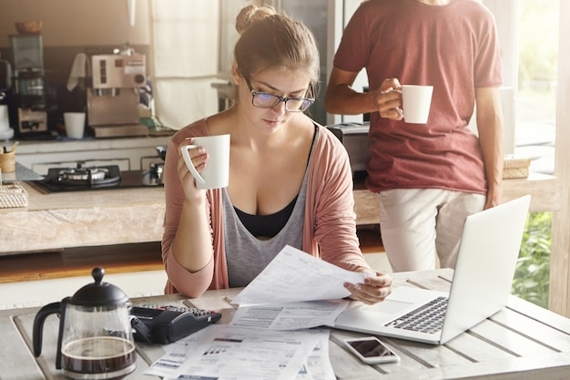 Giovane femmina che tiene tazza di tè in una mano, guardando con espressione seria la carta in un altro Foto Gratuite