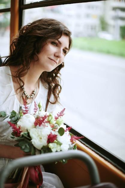 Giovane femmina con fiori seduti vicino alla finestra Foto Premium