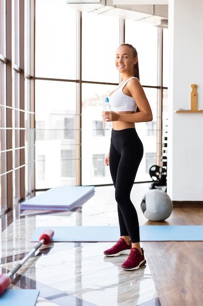 Giovane femmina idratante dopo l'allenamento in palestra Foto Gratuite