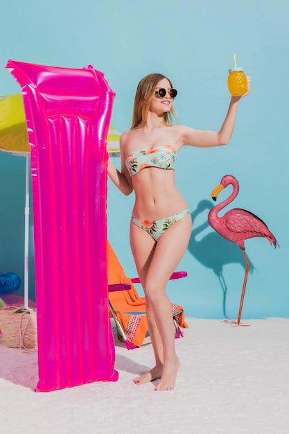 Giovane femmina in piedi con materasso e cocktail Foto Gratuite