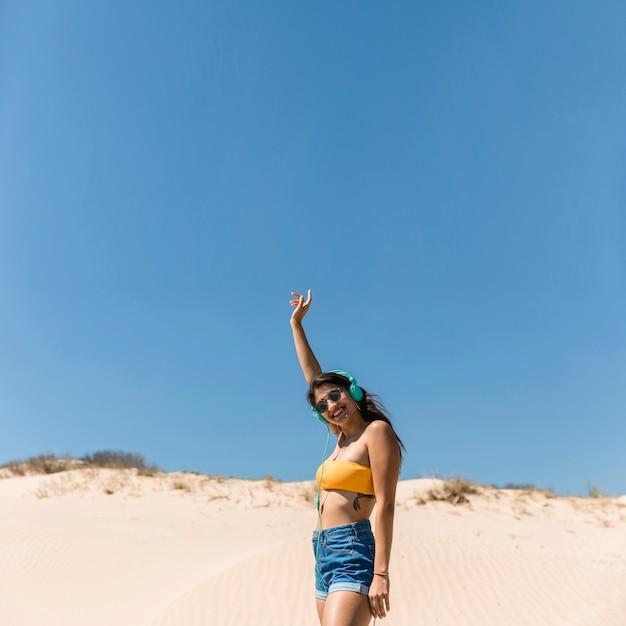 Giovane femmina sorridente in cuffie sulla spiaggia Foto Gratuite