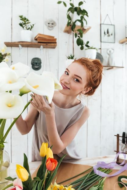 Giovane fiorista che sente l'odore dei fiori bianchi mentre lavora Foto Gratuite