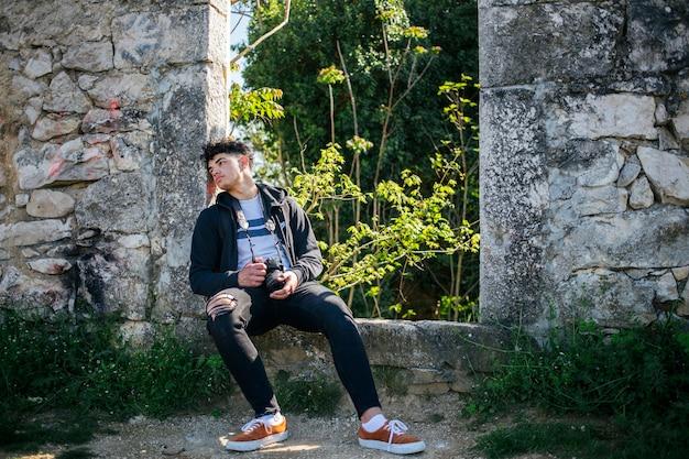 Giovane fotografo faticoso che si siede sulla vecchia parete di pietra con la macchina fotografica della holding Foto Gratuite