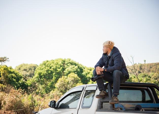 Giovane fotografo seduto sul suo camioncino picking fotografare in montagna. Foto Gratuite
