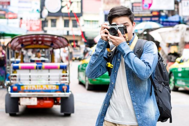 Giovane fotografo turistico asiatico che cattura foto mentre viaggia a bangkok Foto Premium