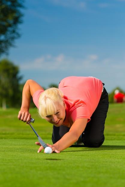Giovane giocatore di golf femminile sul corso che tende a mettere Foto Premium