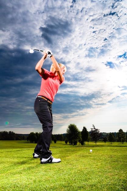 Giovane giocatore di golf in corso facendo swing golf Foto Premium