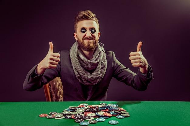 Giovane giocatore di pocker con pollice in alto Foto Premium