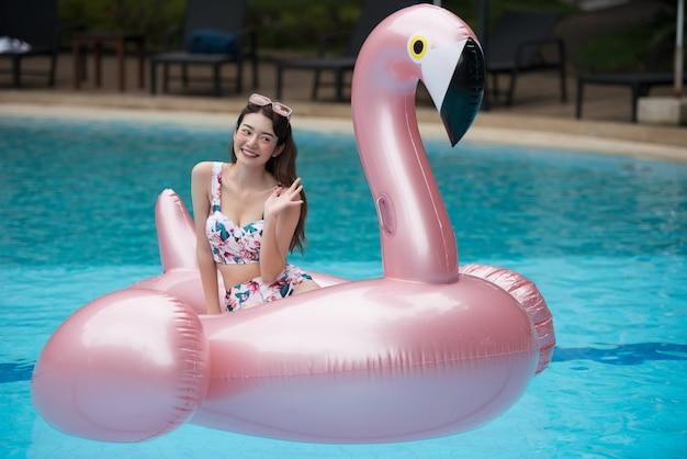 Giovane giro asiatico della donna sul fenicottero gonfiabile gigante nella piscina. Foto Premium