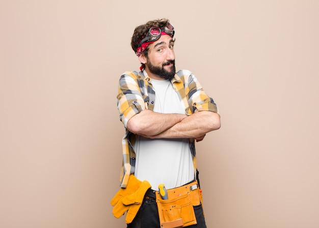 Giovane governante uomo scrollando le spalle, sentendosi confuso e incerto, dubitando con le braccia incrociate e sguardo perplesso contro la parete piatta Foto Premium