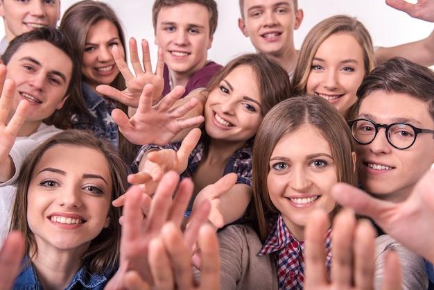 Giovane gruppo di amici sorridente felice su gray Foto Premium