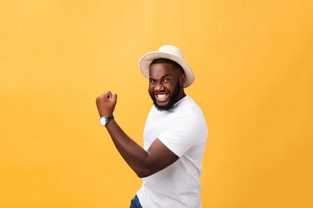 Giovane impiegato afroamericano bello che si sente eccitato, gesturing attivamente, tenendo i pugni serrati Foto Premium
