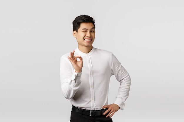 Giovane imprenditore asiatico sorridente allegro con la camicia bianca con il gesto giusto Foto Premium