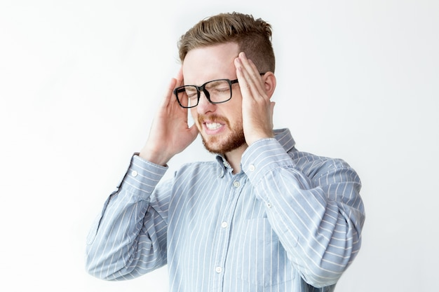 Giovane imprenditore frustrato toccando testa dolorante Foto Gratuite