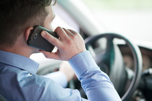 Giovane imprenditore nella sua auto al volante a parlare su un telefono cellulare Foto Premium