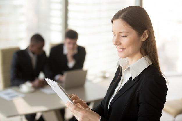Giovane imprenditrice attraente tenendo compressa, guardando a schermo Foto Gratuite