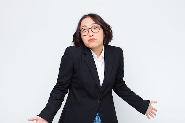 Giovane imprenditrice che si sente incapace e confusa, non avendo idea, assolutamente perplessa con uno sguardo stupido o sciocco contro il muro bianco Foto Premium