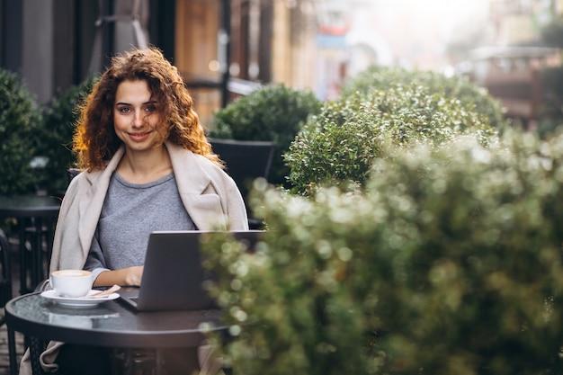Giovane imprenditrice lavorando su un computer fuori dal bar Foto Gratuite