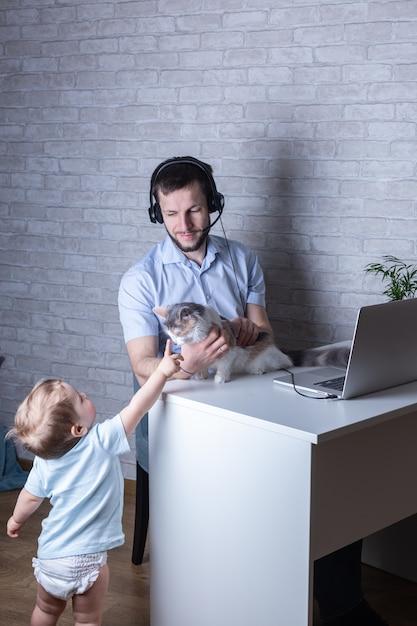 Giovane in cuffia lavora da casa e fa da babysitter con suo figlio neonato e un gatto carezzevole Foto Premium