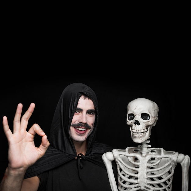 Giovane in mantello nero che sta con lo scheletro e che mostra