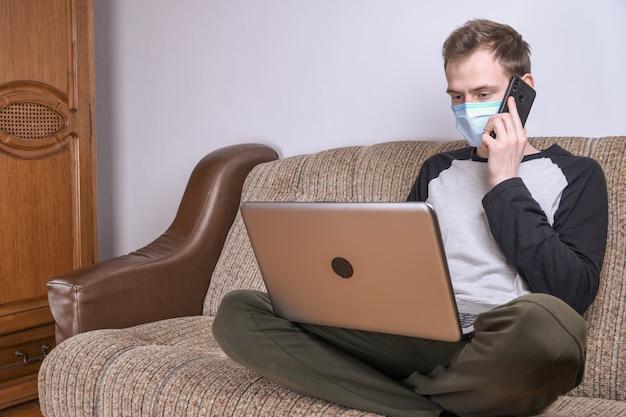 Giovane in maschera medica che lavora a casa nella stanza sul divano utilizzando un computer portatile. quarantena, autoisolamento, protezione da coronavirus. vacanze dal lavoro. Foto Premium