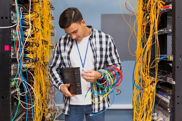 Giovane ingegnere di rete che esamina gli interruttori ethernet Foto Gratuite