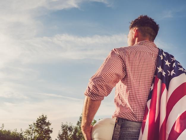 Giovane ingegnere, elmetto protettivo bianco e bandiera americana Foto Premium