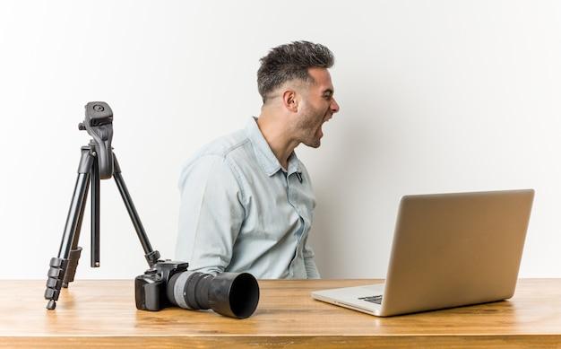 Giovane insegnante di fotografia bello che grida verso uno spazio della copia Foto Premium