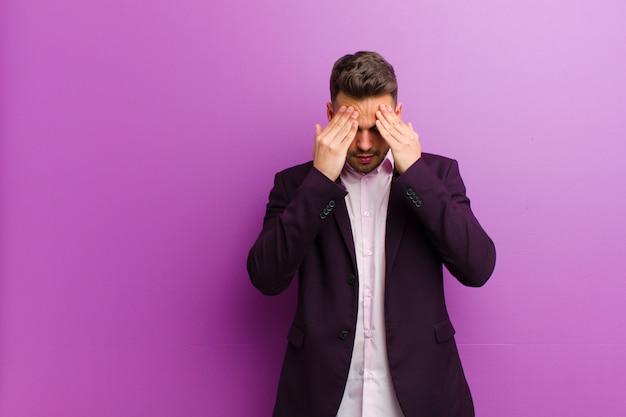 Giovane ispanico che sembra stressato e frustrato, che lavora sotto pressione con mal di testa e turbato da problemi Foto Premium