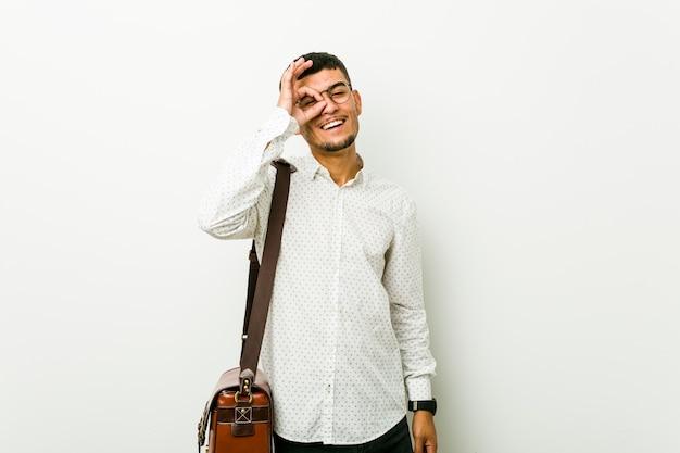 Giovane ispanico uomo d'affari casual eccitato mantenendo ok gesto sull'occhio. Foto Premium