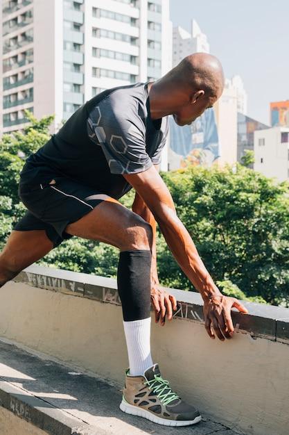 Giovane jogger maschio formazione e facendo allenamento all'aperto in città Foto Gratuite