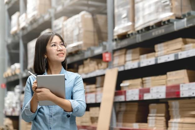 Giovane lavoratore asiatico attraente, proprietario, donna dell'imprenditore che tiene compressa astuta. Foto Premium