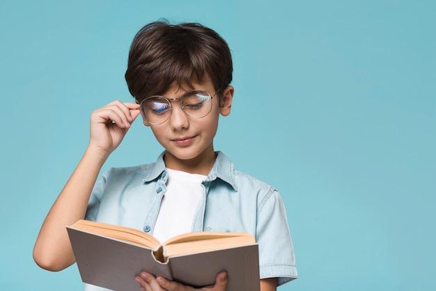 Giovane lettura del ragazzo con copia-spazio Foto Gratuite